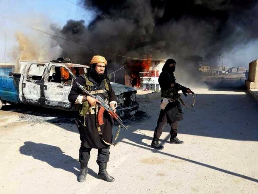 An estimated 3,400 foreign fighters for Islamic State have come from Western countries. Above, Islamic State fighters stand next to a burning vehicle in Iraq.