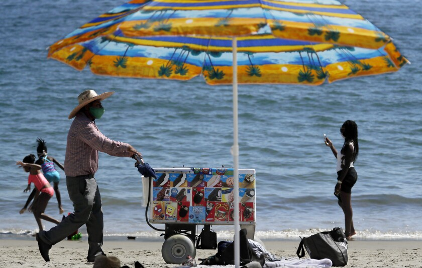 An ice cream vendors pushes a cart along the sand at Junipero Beach in Long Beach on a warm afternoon.