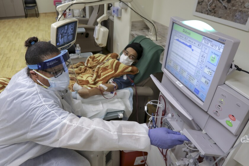 Annie Gibson, a hemodialysis nurse, left, attends to COVID-19 patient  on dialysis.