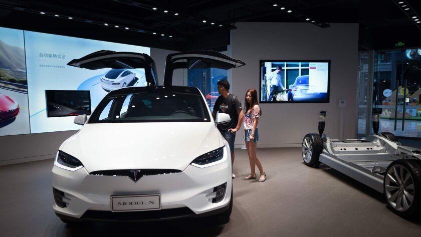 People visit a Tesla showroom in Beijing on July 4,
