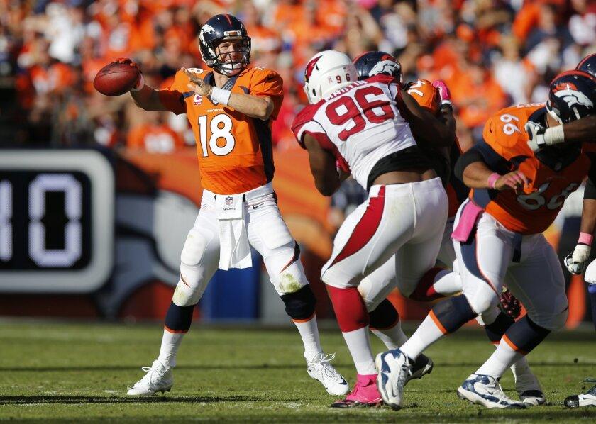 Denver Broncos quarterback Peyton Manning (18) throws as Arizona Cardinals defensive end Kareem Martin (96) pursues during the second half of an NFL football game, Sunday, Oct. 5, 2014, in Denver. (AP Photo/David Zalubowski)