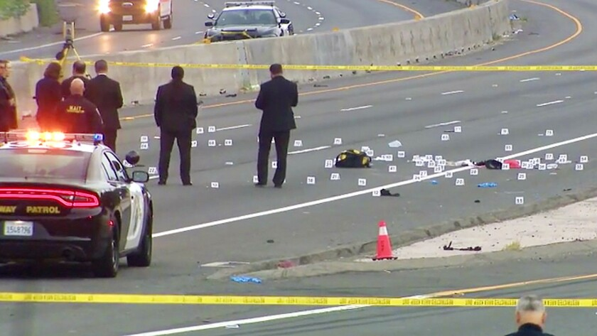 Officers investigate a fatal police shooting on the 710 Freeway in Long Beach early Friday morning.