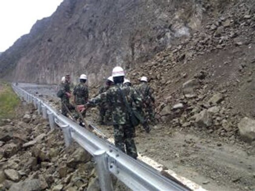 This photo taken by mobile phone camera released by China's Xinhua news agency, shows a landslide triggered by an earthquake on a road in Benzilan Township of Deqen County, southwest China's Yunnan Province Saturday, Aug. 31, 2013. The quake shook several counties in Yunnan and Sichuan provinces Sa