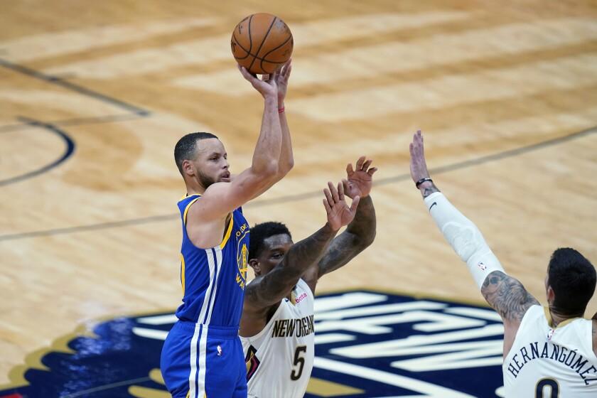 El base de los Warriors de Golden State Stephen Curry lanza el balón mientras lo intentan defender Eric Bledsoe y Willy Hernangomez de los Pelicans de Nueva Orléans en el encuentro del lunes 3 de mayo del 2021. (AP Photo/Gerald Herbert)