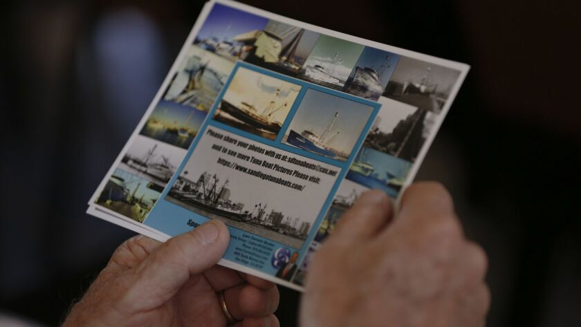A guest in the audience looks over photos of past and present tuna boats. The public was invited to listen to guest panelist talk about the tuna fishing industry in San Diego at Saint Agnes Church in Point Loma.