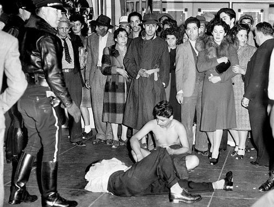 Two young men — one badly beaten, the other stripped of his clothes — draw a crowd during the Zoot Suit Riots in 1943.