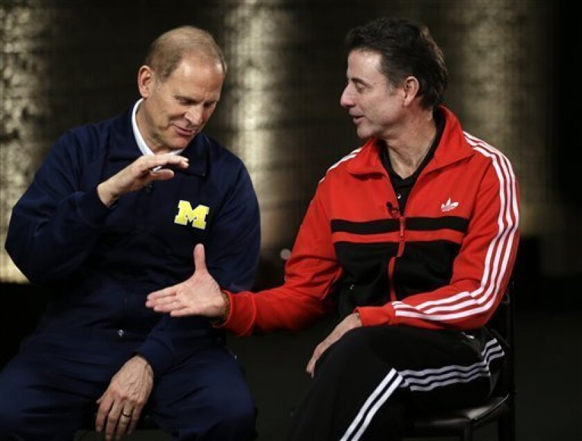 Louisville head coach Rick Pitino and Michigan head coach John Beilein, left, participate in a television interview for their NCAA Final Four tournament college basketball game Sunday, April 7, 2013, in Atlanta. Louisville plays Michigan in the championship game on Monday. (AP Photo/David J. Philli