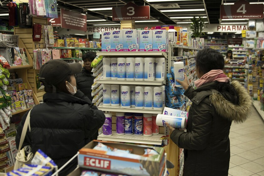 Customers look at sanitizing wipes on the shelves of a pharmacy in New York on Wednesday, March 4, 2020. As coronavirus infections spread across the globe, everybody has to make a decision: How worried should I be about getting infected, and what should I do about it? (AP Photo/Marshall Ritzel)