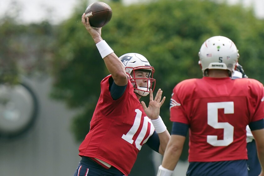 New England Patriots quarterback Mac Jones (10) winds up for a pass as quarterback Brian Hoyer (5) looks on during NFL football practice, Wednesday, Sept. 15, 2021, in Foxborough, Mass. (AP Photo/Steven Senne)