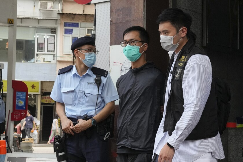 Simon Leung Kam-wai, center, a committee member of the Hong Kong Alliance in Support of Patriotic Democratic Movements of China, is escorted by police during an investigation of the June 4th Museum in Hong Kong. 12 Hong Kong pro-democracy activists pleaded guilty on Thursday to participating and inciting others to take part in last year's unauthorized candlelight vigil to mark the bloody Tiananmen Square crackdown, amid an ongoing crackdown on dissent in Hong Kong which has seen dozens of activists arrested. (AP Photo/Kin Cheung)