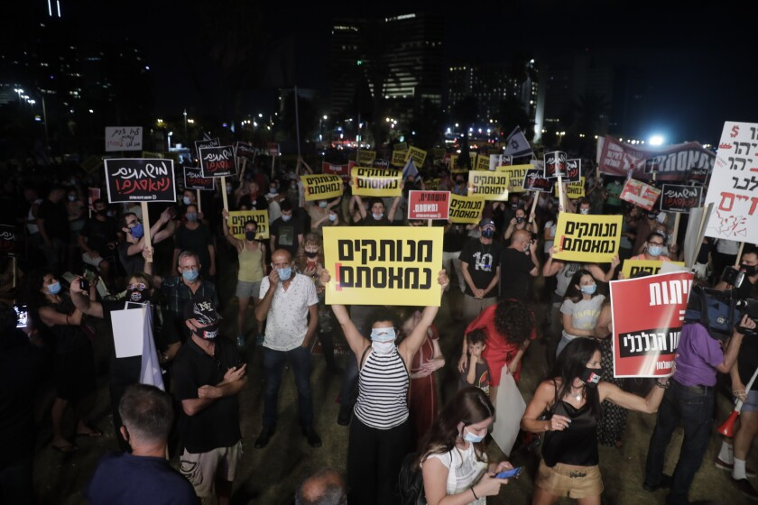 """Israelis hold signs during a protest In Tel Aviv, Israel, Saturday, July 18, 2020. The sign says in Hebrew reads:""""Out if touch, we are fed up."""" (AP Photo/Sebastian Scheiner)"""