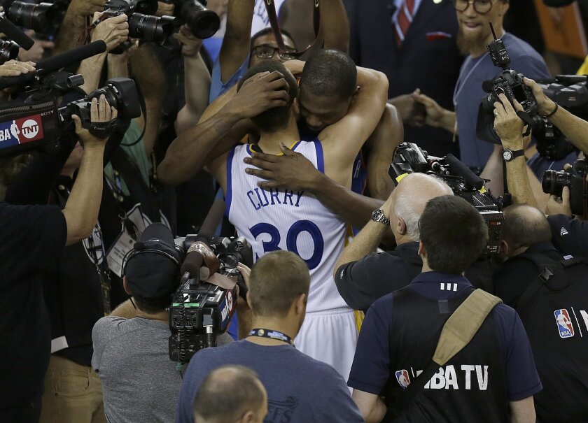 Golden State Warriors guard Stephen Curry (30) hugs Oklahoma City Thunder forward Kevin Durant after Game 7 of the NBA basketball Western Conference finals in Oakland, Calif., Monday, May 30, 2016. The Warriors won 96-88. (AP Photo/Ben Margot)