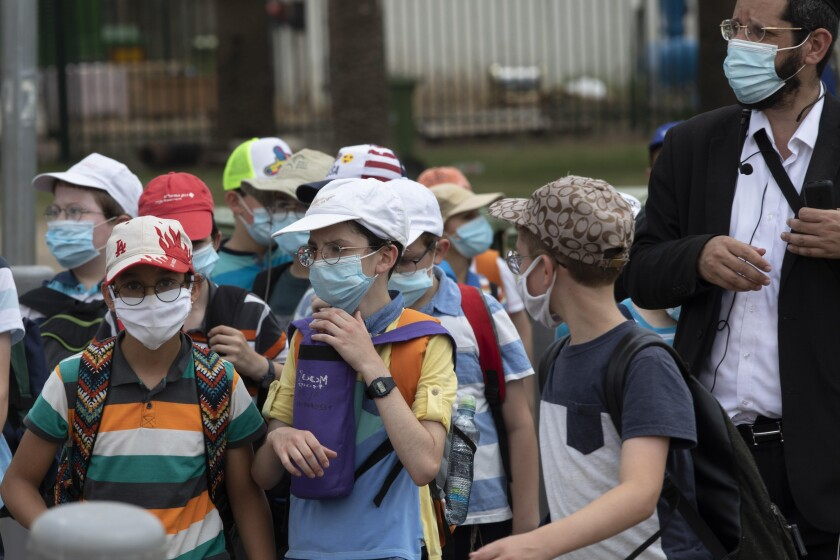 """File---File picture taken July 6, 2020 shows Israeli school children wearing face masks to help prevent the spread of the coronavirus as they walk in Tel Aviv, Israel. As Germany's 16 states start sending millions of children back to school in the middle of the global coronavirus pandemic, those used to the country's famous """"Ordnung"""" are instead looking at uncertainty, with a hodgepodge of regional regulations that officials acknowledge may or may not work. (AP Photo/Sebastian Scheiner,File)"""