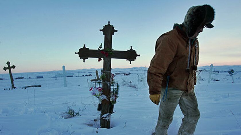 PAYING RESPECTS: Thomas Cheemuk visits the grave of his brother John, who killed himself in 1999, in a cemetery overlooking the Alaska village of St. Michael in February.