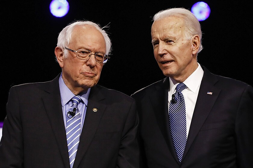 Bernie Sanders, left, and Joe Biden chat before a Democratic presidential debate in Charleston, S.C., on Feb. 25.