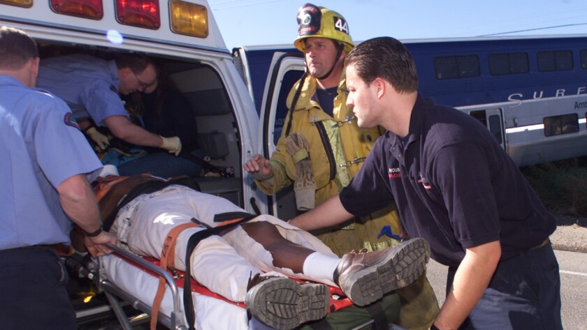 MEDICS––A Ventura County firefighter, center, and AMR paramedic, right, tend to a man who was injure