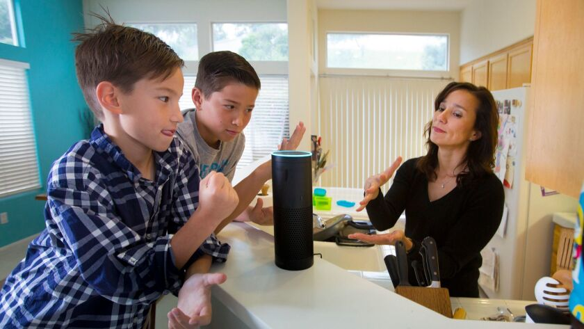 """Family members play a game of rock-paper-scissors with """"Alexa,"""" their Amazon Echo wireless speaker and voice command personal assistant, at their home in San Diego's Scripps Ranch community."""