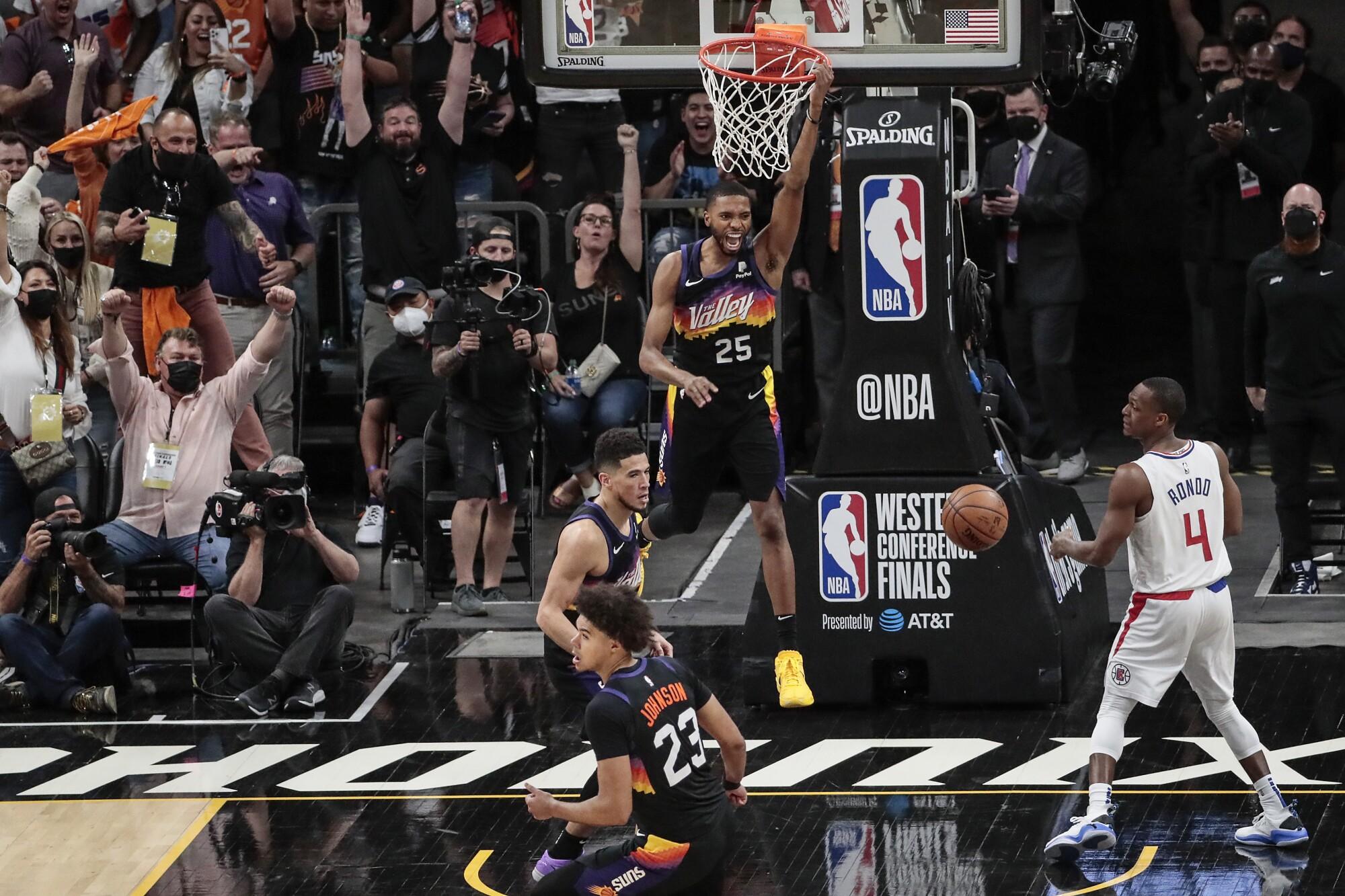 Phoenix forward Mikal Bridges celebrates while dunking over Clippers guard Rajon Rondo.