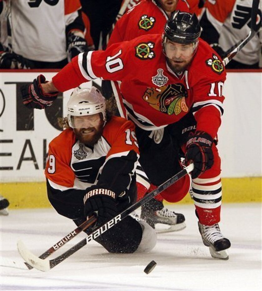 Philadelphia Flyers left wing Scott Hartnell (19) dives for the puck as Chicago Blackhawks center Patrick Sharp (10) heads down the ice in the first period of Game 5 of the NHL Stanley Cup hockey finals on Sunday, June 6, 2010, in Chicago. (AP Photo/Nam Y. Huh)