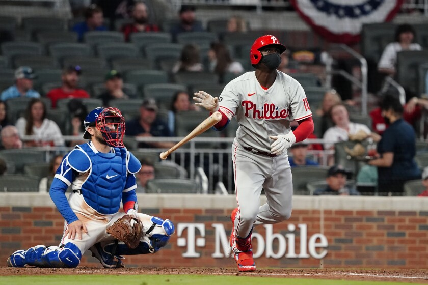Philadelphia Phillies' Didi Gregorius (18) follows through on three-run home run as Atlanta Braves catcher Travis d'Arnaud (16) looks on in the fourth inning of a baseball game Sunday, April 11, 2021, in Atlanta. (AP Photo/John Bazemore)