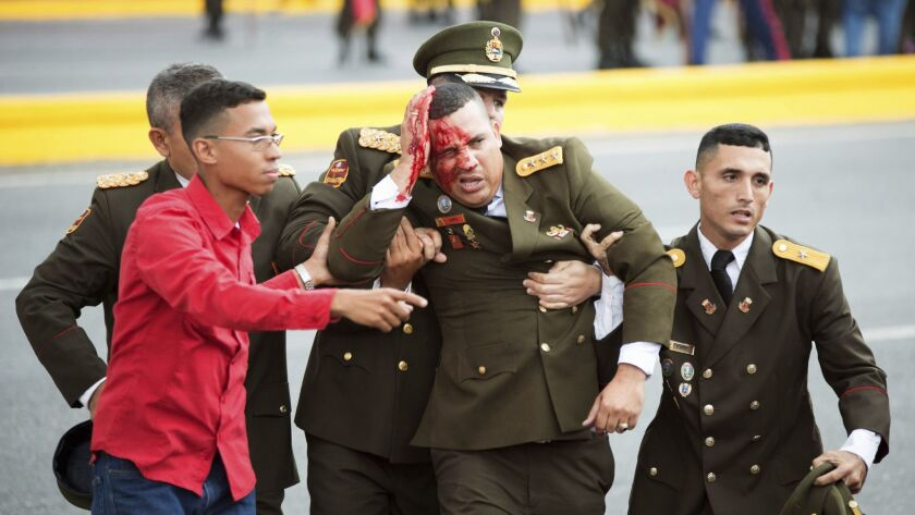 One of the seven members of the Venezuelan military injured in the attack during the president's speech is helped away in Caracas on Saturday.