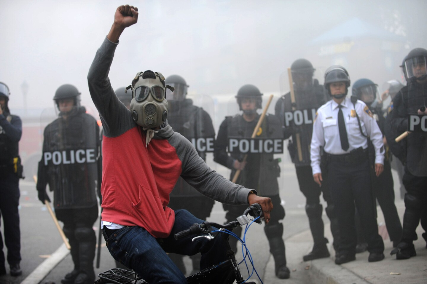 A protestor rides his bike in front of a police line at North and Pennsylvania Avenues on the day of Freddie Gray's funeral. Riots and looting broke out throughout the city.