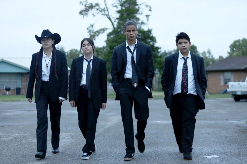 Four teens in dark suits, white shirts and ties striding toward the camera on pavement