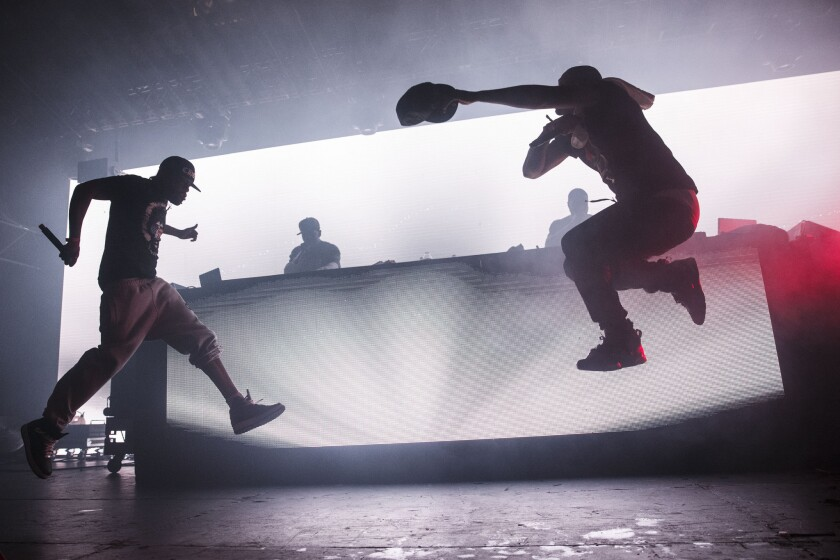 The silhouettes of Method Man and Redman jumping in the air while performing.