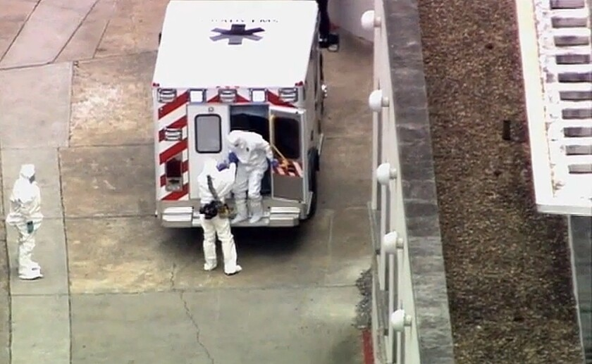 With all involved wearing full protective gear, a man believed to be Ebola patient Dr. Kent Brantly is helped from an ambulance at Emory University Hospital in Atlanta in August.