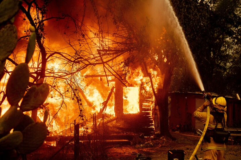 A firefighter sprays water on a burning home as the Kincade Fire burns through the Jimtown community of unincorporated Sonoma County, Calif., on Thursday, Oct. 24, 2019.