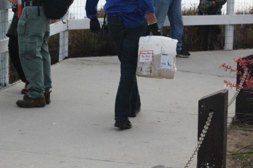 A Blue Eagle worker delivers excrement-eating product to workers on the cliffs above La Jolla Cove.