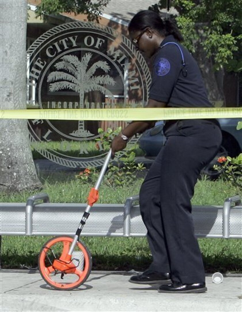 A City of Miami police officer takes measurements at the scene where a shooting took place in Miami, Monday, July 6, 2009. As many as three gunman stormed a birthday party on the edge of downtown Miami and opened fire early Monday morning, shooting 12 people and causing a chaotic scramble as they tried to flee the scene, authorities said. Three of the wounded were hospitalized in critical condition, police spokesman Det. William Moreno said. Another person fleeing the home was struck by a vehicle and was in stable condition. Police are searching for the suspects. (AP Photo/Alan Diaz)