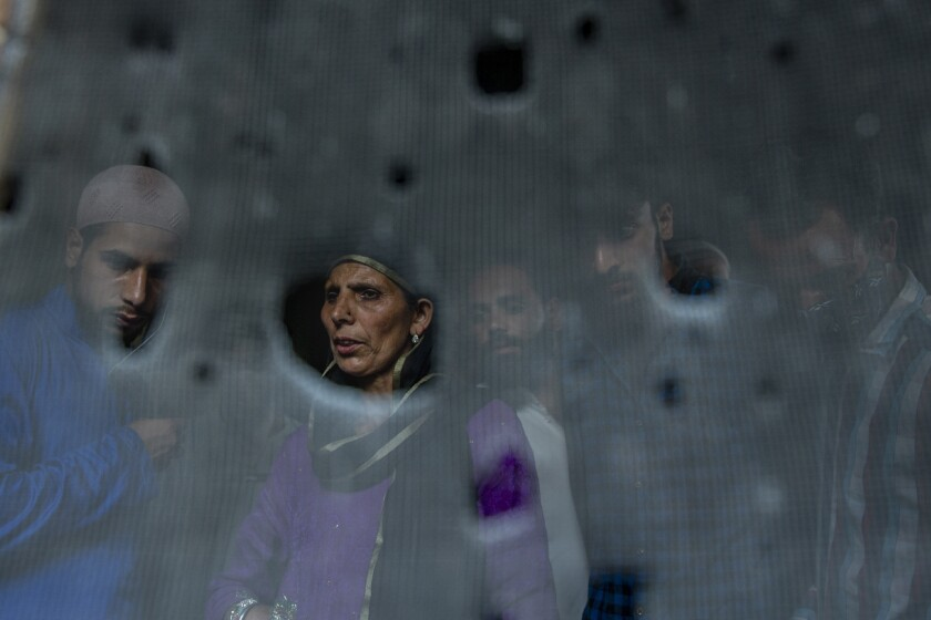 Kashmiri villagers are seen through the bullet ridden iron mesh of a window of the residential house where suspected rebels were taking refuge, after a gunfight in Pulwama, south of Srinagar, Indian controlled Kashmir, Friday, July 2, 2021. Five suspected rebels and an army soldier were killed in a gunfight in Indian-controlled Kashmir on Friday, officials said, as violence in the disputed region has increased in recent weeks. (AP Photo/ Dar Yasin)
