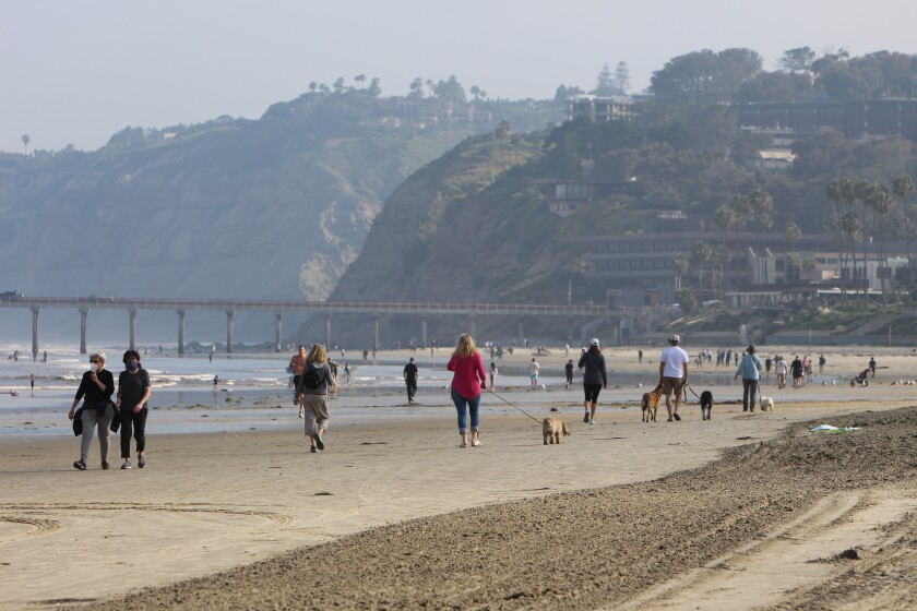 Walkers stroll along La Jolla Shores beach at 7:30 a.m. April 27 after the beach was reopened following a closure due to coronavirus restrictions.
