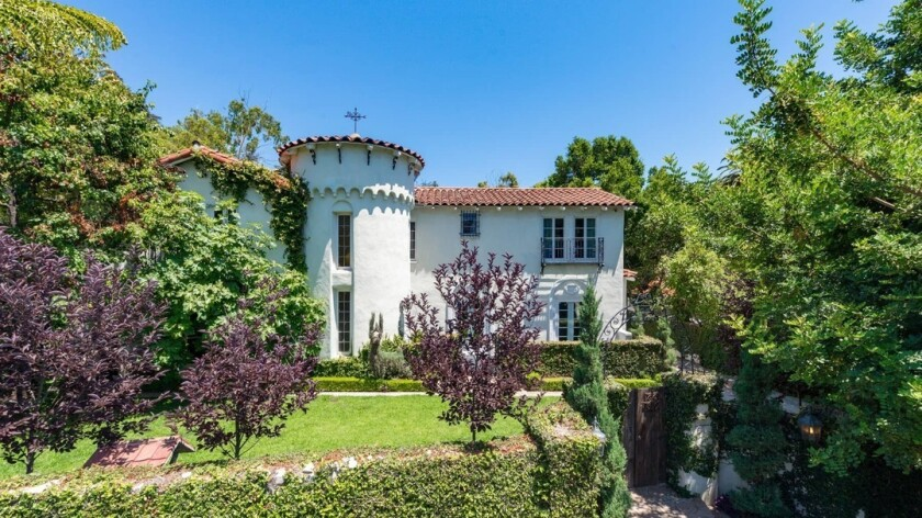 The roughly 4,150-square-foot Spanish Revival-style house features a turret entry, original tile and a guesthouse.