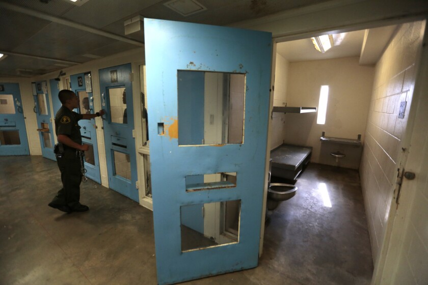 A deputy checks on one of the inmates in the High Observation Mental Health Housing unit at the Twin Towers Correctional Facility in 2015.