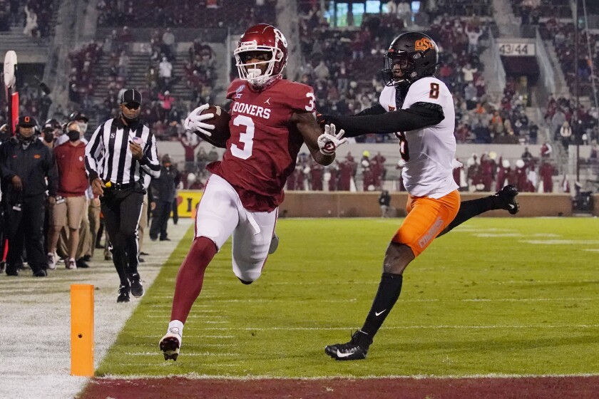 Oklahoma tight end Mikey Henderson (3) carries for a touchdown past Oklahoma State defender Rodarius Williams (8) during the first half of an NCAA college football game in Norman, Okla., Saturday, Nov. 21, 2020. (AP Photo/Sue Ogrocki)