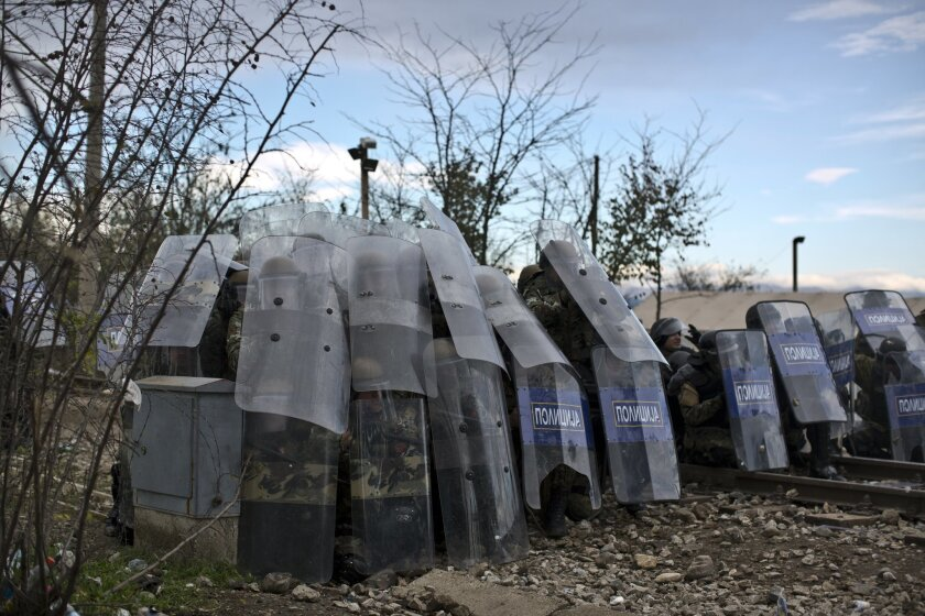 Macedonian policemen shelter behind their shields from stones hurled by migrants during clashes at the Greek-Macedonian border, near the northern Greek village of Idomeni, Saturday, Nov. 28, 2015. Tension has flared on the Greek side of the Greece-Macedonia border when a migrant who was stopped from crossing into Macedonia, suffered severe burns when he climbed on top of a stationary train carriage and touched a overhead power cable. (AP Photo/Muhammed Muheisen)