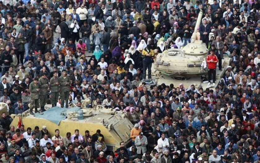 Anti-government protesters, and Egyptian Army soldiers on top of their vehicles, make traditional Muslim Friday prayers at the continuing demonstration in Tahrir Square in downtown Cairo, Egypt, Friday, Feb. 11, 2011. (AP Photo/Ben Curtis)
