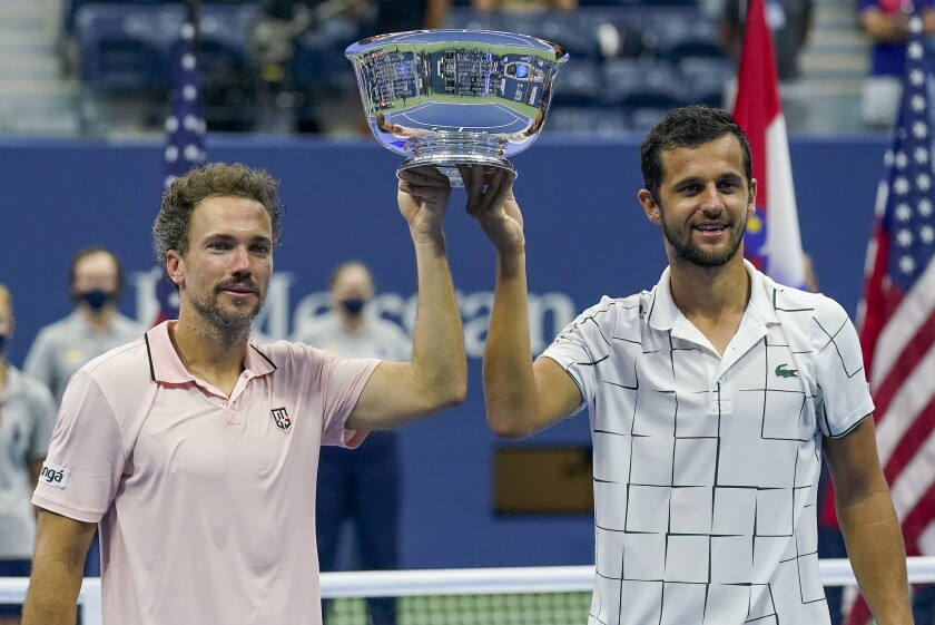 Bruno Soares, of Brazil, left, and Mate Pavic, of Croatia, hold up the championship trophy after winning the men's doubles final against Wesley Koolhof, of the Netherlands, and Nikola Mektic, of Croatia, during the US Open tennis championships, Thursday, Sept. 10, 2020, in New York. (AP Photo/Seth Wenig)