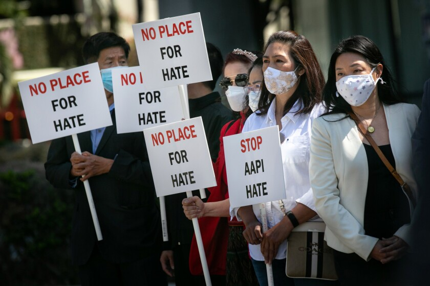 Asian community members hold signs against hate at a news conference in Los Angeles on Monday.