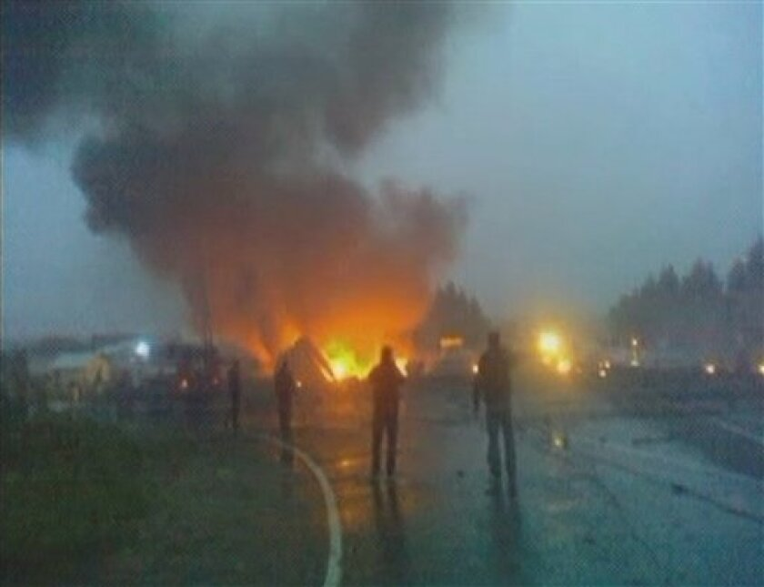 In this image taken from video footage of AMVID via APTN, flames rise from the wreckage of a Tu-134 plane which crashed on a highway in Petrozavodsk, northwestern Russia, early Tuesday, June 21, 2011. The passenger jet crashed in heavy fog and burst into flames late Monday on the highway, just short of a runway whose fog lights had failed, killing 44 people, officials said. (AP Photo/AMVID via APTN)