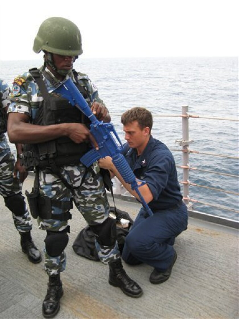 This image taken Saturday, Feb. 13, 2010 shows Petty Officer 3rd Class John Dawson, 22, of Franklin Furnace, Ohio, USA, right, helping a Nigerian special forces fighter with his gear before a training exercise onboard the USS Samuel B. Roberts off the coast of Nigeria. The U.S. Navy offered training to the Nigerian navy as worries mount of increasingly violent pirate attacks along the West African coast. The 530 miles (853 kilometers) of coastline along Nigeria, Africa's most populous nation, remains a lucrative target for pirates. Energy company barges and vessels crowd the waters off of the oil-rich Niger Delta, which provides the U.S. one of its top sources for easily refined crude oil for gasoline. The weapon, painted blue, is fake plastic used for training.(AP Photo/Jon Gambrell )