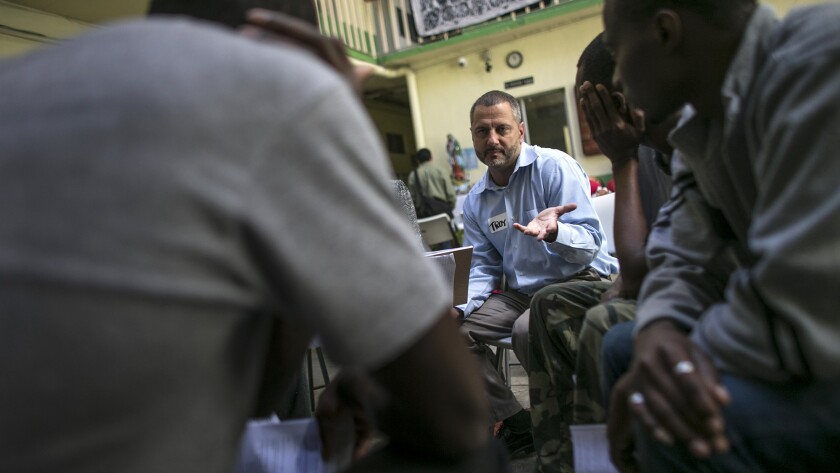 Attorney Troy Elder, speaking Creole, talks to a group of Haitian men seeking to enter the United States.