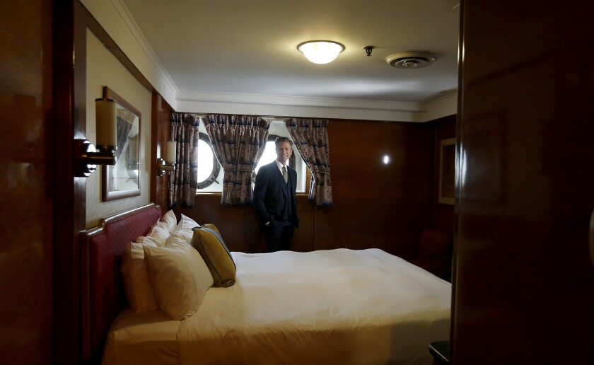 Woods, a principal of a real estate development company called Urban Commons, walks through a state room aboard Queen Mary