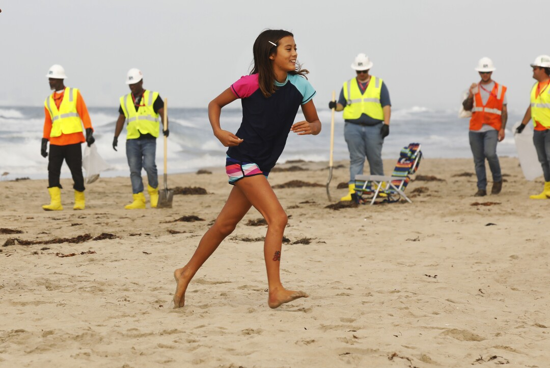 A child runs across the sand with a cleanup crew in the background