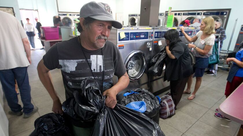 A man brings in bags of clothes to be cleaned.