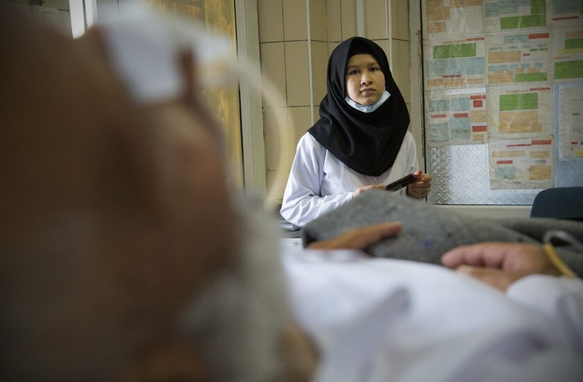 A young student nurse at the National Military Hospital sat beside a patient waiting to be seen by a doctor in May.
