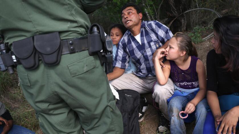 Agente de la Patrulla Fronteriza habla con inmigrantes de Centro América que buscan asilo en Estados Unidos.
