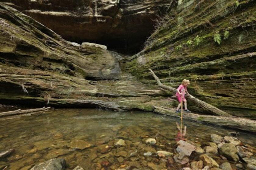 In this April, 8, 2013 photo, Lucy Childers, 6, plays on the rock formations at Ferne Clyffe State Park in Goreville, Ill. Southern Illinoisans have hopes and fears surrounding the high-volume oil and gas drilling that may be starting in the Shawnee National Forest. Many people are beginning to brace for change as state lawmakers consider regulations that would allow energy companies to begin drilling deep in the southern Illinois bedrock for oil and natural gas, using a process known as high-vo